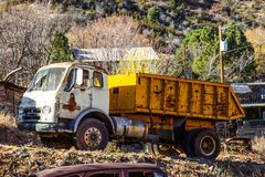 Vintage Dump Truck In Salvage Yard. Vintage Rusty Dump Truck Parked On Side Of Hill In Salvage Yard Royalty Free Stock Image