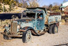 Vintage rusty dump truck. Vintage retro rusted dump truck with flat tires in early morning royalty free stock photo