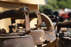 Vintage rusty irons all in a row. Primitive irons sit abandoned in the sun Stock Photo