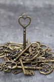Vintage rusty key standing. On grunge wooden background Stock Photo