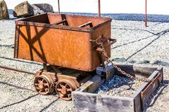 Vintage Rusty Ore Cart Used In Mining Operations. Vintage Rusty Ore Cart Once Used In Mining Operations Chained To Wooden Box Stock Image