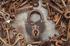Vintage rusty padlock surrounded by old keys Stock Photos