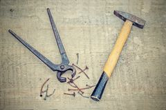 Vintage rusty pliers, hammer and nails, filtered Royalty Free Stock Images