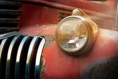 Vintage rusty red truck car with a new headlight in the sunshine Stock Image