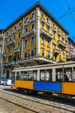 Vintage 1930s style Milan, Italy tram. Juxtaposition against yellow traditional building and blue sky Royalty Free Stock Image