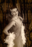 Vintage 1920s woman with boa. Beautiful vintage 1920s lady wearing a headband and white feather boa royalty free stock images