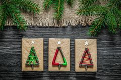 Vintage sacking fir branch Christmas present box on wooden board.  Royalty Free Stock Photos