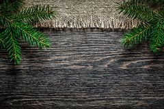 Vintage sacking pine branch on wooden board Christmas background.  Royalty Free Stock Images
