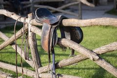 Vintage saddle on rural fence. Ranch scene. Wild west royalty free stock photo
