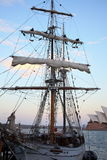 Striking sails on sailing ship at twilight Stock Photos