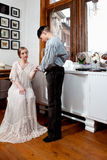 Vintage sailor and girl in victorian dress. Man dressed in old sailor clothing asking for the hand of a girl in a vintage victorian dress sitting in a room with Stock Photo