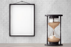 Vintage Sand hourglass in front of Brick Wall with Blank Frame. Extreme closeup Stock Photography
