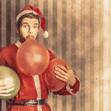 Vintage santa preparing for christmas party. Vintage textured christmas card concept on a santa man blowing up party balloon in preparation for a happy holiday Stock Images