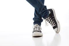 Vintage, sapatas atléticas da antiguidade sobre com calças de brim Fotografia de Stock Royalty Free