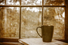 Vintage scene of cup in front of window. A black coffee cup sits on a table in front of a paned window.  A vintage filter is applied Stock Photo