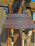 Vintage School Bell. An old cast iron school bell hanging by chains from some old weathered timber Royalty Free Stock Images
