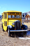 Vintage School Bus. A beautiful antique school bus sits in a field in front of a log cabin in rural Colorado Stock Image