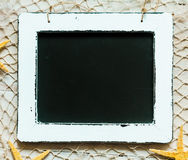 Vintage school slate with fishing net and starfish royalty free stock photos