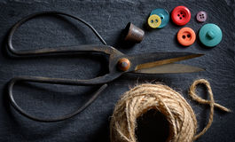 Vintage scissors and buttons. Vintage scissors with a roll of twine and buttons Royalty Free Stock Photo