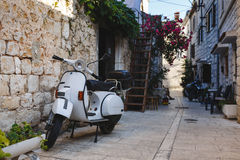 Vintage scooter parked in a narrow street in croatia Royalty Free Stock Photos