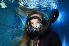 Vintage scuba woman. Scuba woman with black neoprene dive suit and spear gun underwater Stock Photography
