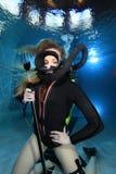 Vintage scuba woman. Scuba woman with black neoprene dive suit and spear gun underwater Stock Photo