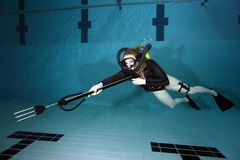 Vintage scuba woman. Scuba woman with black neoprene dive suit and spear gun underwater Royalty Free Stock Images