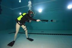 Vintage scuba woman. Scuba woman with black neoprene dive suit and spear gun underwater Stock Images