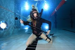 Vintage scuba woman. Scuba woman with black neoprene dress and spear gun diving underwater Royalty Free Stock Images
