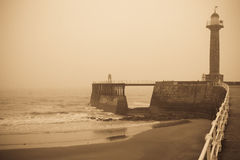 Vintage seaside pier. Whitby West Pier and Harbour in thick fog. Yorkshire, England Stock Photography