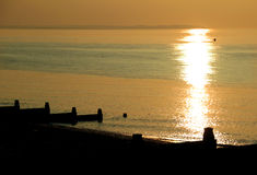 Vintage sepia seaside sunset. Photo of a setting sun over the bay of tankerton at whitstable in kent. silhouetted breakwaters with a vintage sepia tone to the Stock Photography