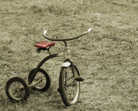 Vintage Sepia Tricycle. Sepia Toned Vintage Tricycle with Red colored seat Royalty Free Stock Images