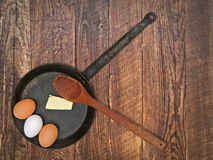 Vintage set for frying eggs over wooden table Stock Image
