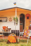 Vintage seventies orange caravan with front tent and camping acc Royalty Free Stock Photos