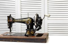 Vintage sewing machine is standing on the white table stock image