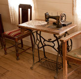 Vintage sewing machine. An old fashioned sewing machine on worn table stands in weatherboard cottage with bare wooden floorboards Stock Images
