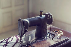 Vintage sewing machine with fabric and scissor in the room. Vintage color tone Royalty Free Stock Photo
