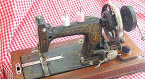 Vintage Sewing Machine. This photo shows a well used 1920s Vintage Sewing Machine on a red gingham background. This photo could be used to promote collectable Stock Photos