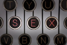 Vintage Sex. Close up of old typewriter keyboard with scratched chrome keys with black centers and white letters. Lighting and focus are centered on for keys Royalty Free Stock Image