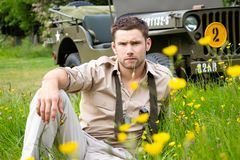 Handsome American WWII GI Army officer in uniform relaxes in a meadow of flowers in front of Willy Jeep. Vintage, American Soldier, SGT in world war 2 officer`s royalty free stock images