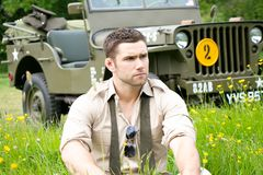 Handsome American WWII GI Army officer in uniform relaxes in a meadow of flowers in front of Willy Jeep. Vintage, American Soldier, SGT in world war 2 officer`s royalty free stock photo