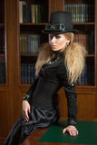 Vintage sexy girl next to the bookcase, gothic Stock Image