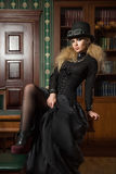 Vintage sexy girl next to the bookcase, gothic Royalty Free Stock Photo