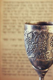 Vintage shabbath silver cup of wine in front of torah prayer book Stock Photos