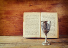 Vintage shabbath silver cup of wine in front of torah prayer book Stock Photo