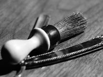 Vintage shaving brush and blade. Black and white view of shaving brush and vintage sharpened shaving blade for men Stock Images