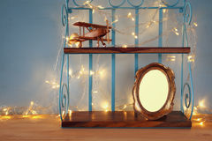 Vintage shelf with old wooden plane toy and blank photo frame Royalty Free Stock Photo