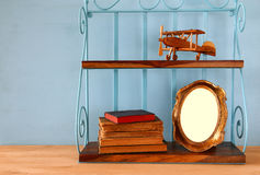 Vintage shelf with old wooden plane toy, books and blank photo frame Royalty Free Stock Photos