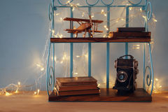 Vintage shelf with old wooden plane toy, books and decorative camera Stock Photography