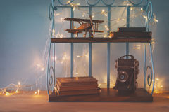 Vintage shelf with old wooden plane toy, books and decorative camera Stock Photos